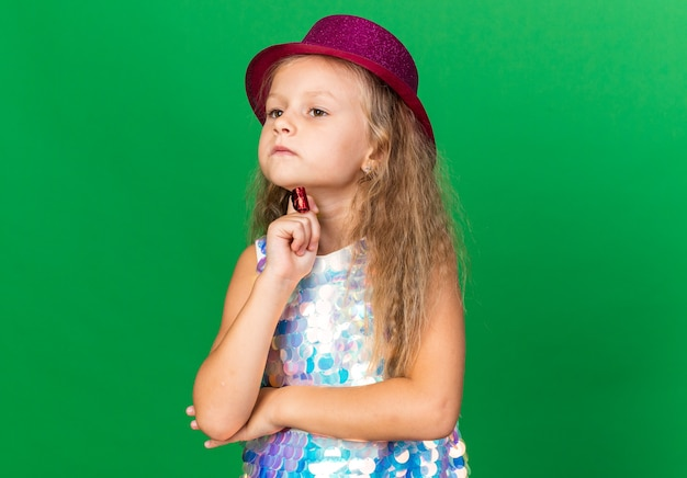 Thoughtful little blonde girl with purple party hat putting hand on chin holding party whistle isolated on green wall with copy space