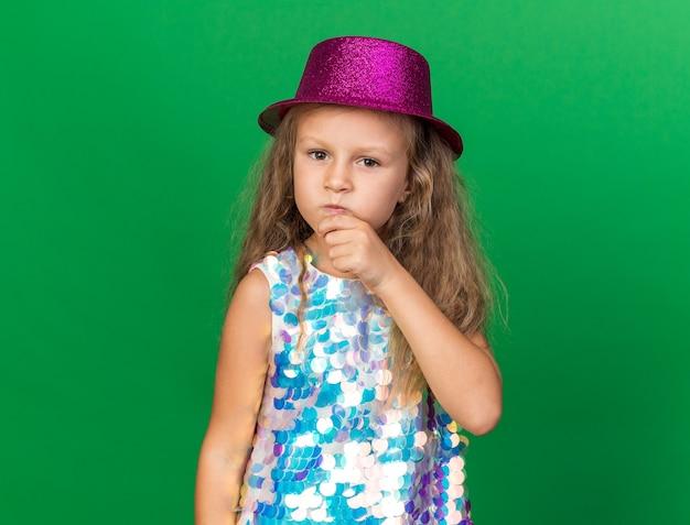 あごに手を置き、コピースペースで緑の壁に孤立して見える紫色のパーティハットを持つ思いやりのある小さなブロンドの女の子