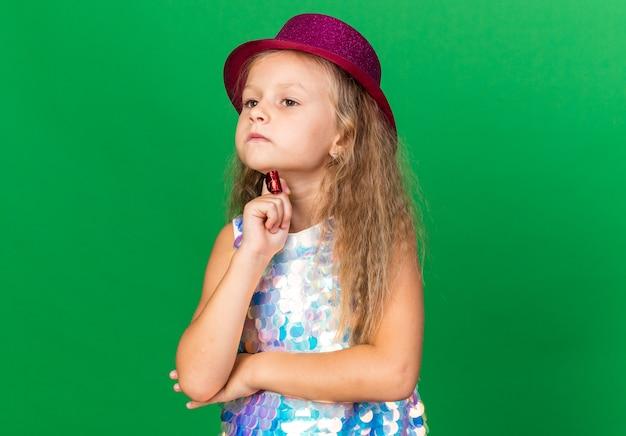 コピースペースと緑の壁に分離されたパーティーの笛を保持しているあごに手を置く紫色のパーティハットを持つ思いやりのある小さなブロンドの女の子