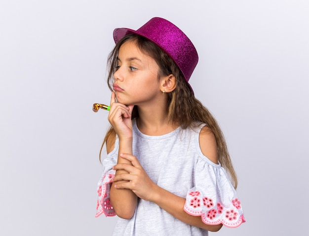 Thoughtful little caucasian girl with purple party hat putting hand on chin holding party whistle and looking at side isolated on white wall with copy space