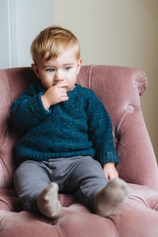 Thoughtful little child sits on comfortable armchair, thinks about something