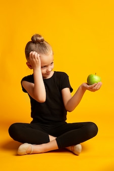 Thoughtful little dancer with apple during break