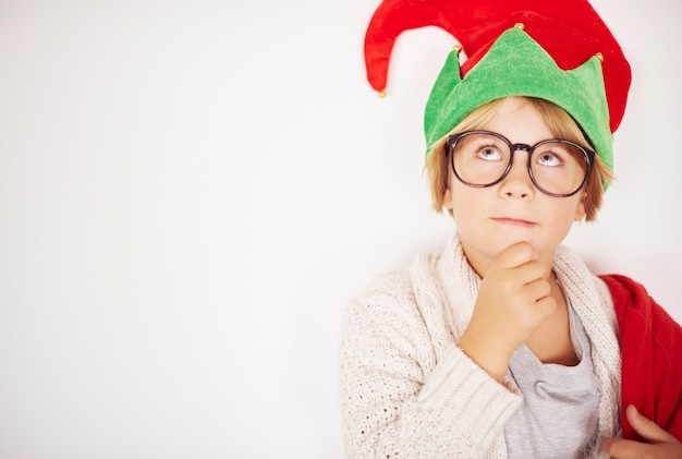 Thoughtful little elf in front the wall