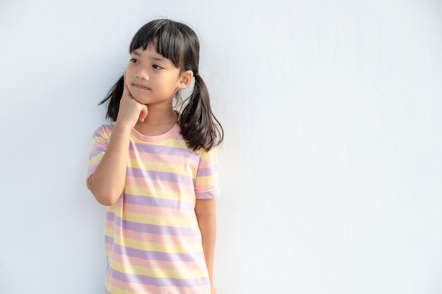 Thoughtful little girl child touch chin with finger thinking or considering, pensive lovely daughter making decision imagining idea posing isolated on white background