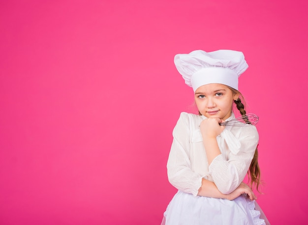 Thoughtful little girl cook with whisk
