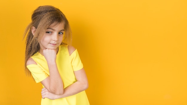 Thoughtful little girl in dress on yellow background