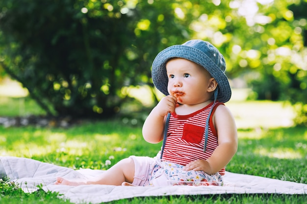 Thoughtful little girl eating fresh red strawberries baby outdoors at summertime on green nature