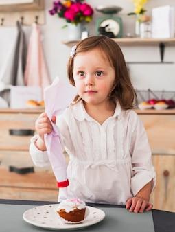 Thoughtful little girl making cupcake