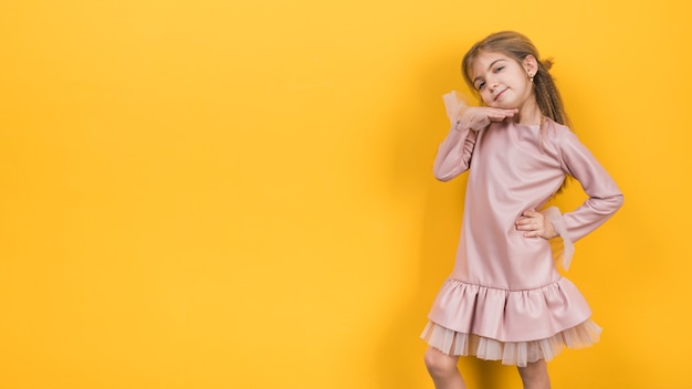 Thoughtful little girl posing on yellow background