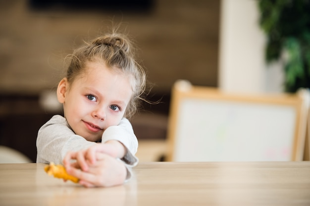 Задумчивая маленькая девочка сидит за столом