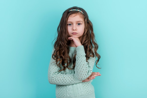 Thoughtful little girl standing on blue background