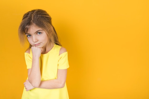 Thoughtful little girl standing on yellow background