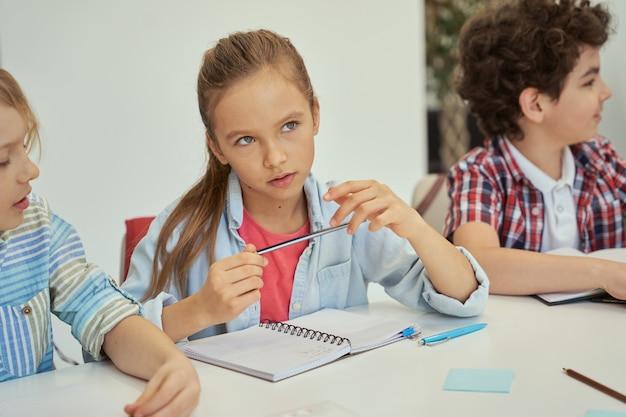 Задумчивая маленькая школьница смотрит в сторону с карандашом во время учебы, сидя за столом в