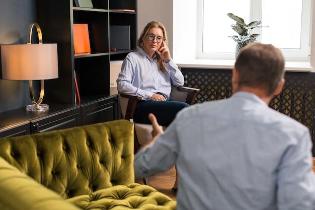 思いやりのある表情。彼女と話している男の前で肘掛け椅子に座っている穏やかな魅力的なブロンドの女性