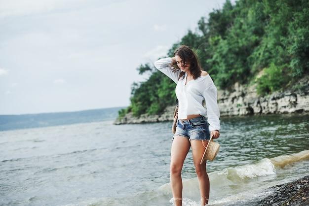 思いやりのある表情。木々と崖の背景とビーチでポーズをとってゴージャスなモデルの女の子。
