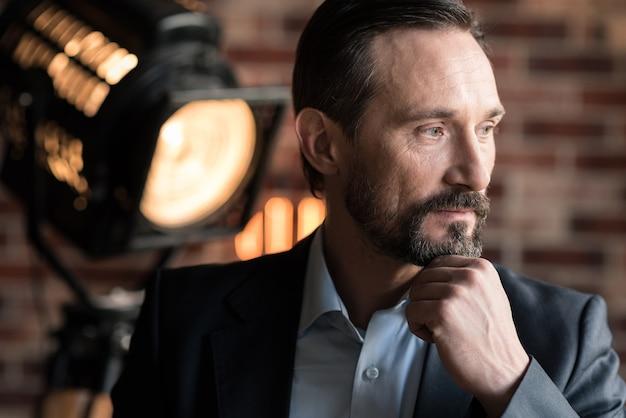 Задумчивый взгляд. красивый задумчивый бородатый бизнесмен держится за подбородок и смотрит налево, думая о чем-то