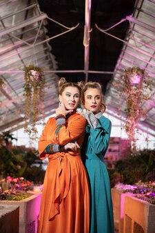 思慮深い表情。ポーズをとりながら温室で一緒に立っている素敵な思いやりのある女性