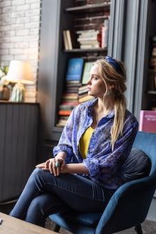 Задумчивый взгляд. милая молодая женщина сидит в кресле, думая о своей жизни