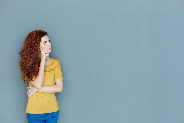 思いやりのある表情。あごに触れて脇を見ながら頭を回す気持ちのいい素敵な若い女性