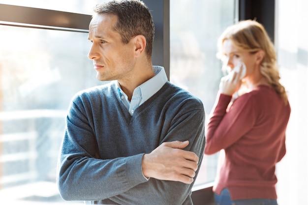 思いやりのある表情。彼のガールフレンドと喧嘩をしながら、クロスハンドで立って窓を覗き込んでいる悲しい陽気で不幸な男