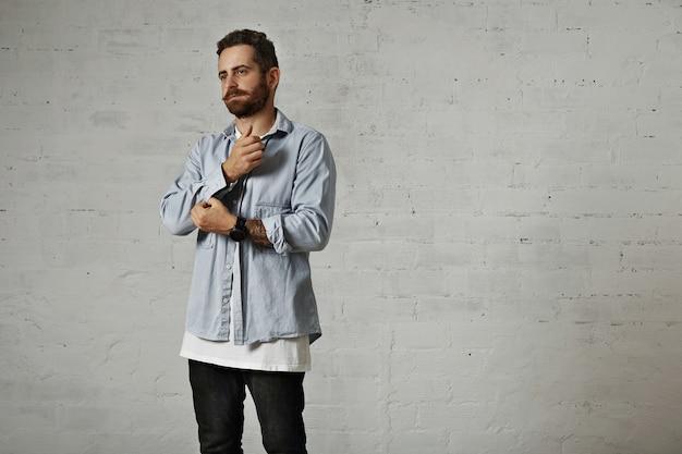 Riflessivo giovane modello alla ricerca alla moda con la barba e le braccia tatuate che sbottonano una manica della sua camicia di jeans chiaro isolato su bianco
