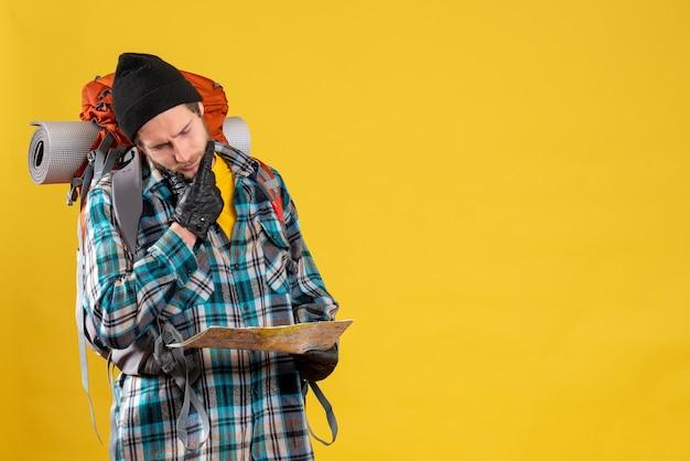 Camper maschio premuroso con guanti di pelle e zaino con mappa