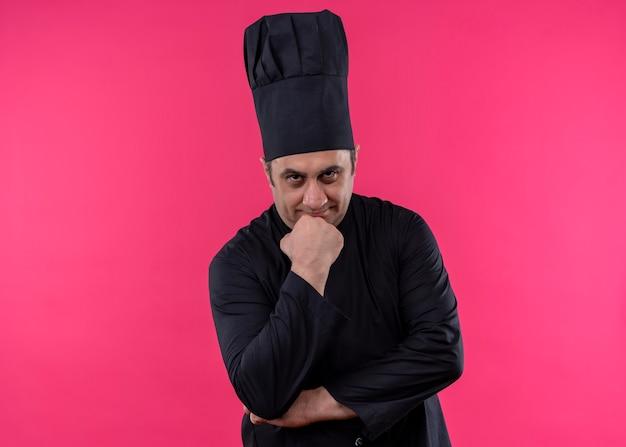 思いやりのある男性シェフは、ピンクの背景の上に立っている物思いにふける表情で顎に手でカメラを見て黒い制服を着て帽子を調理します