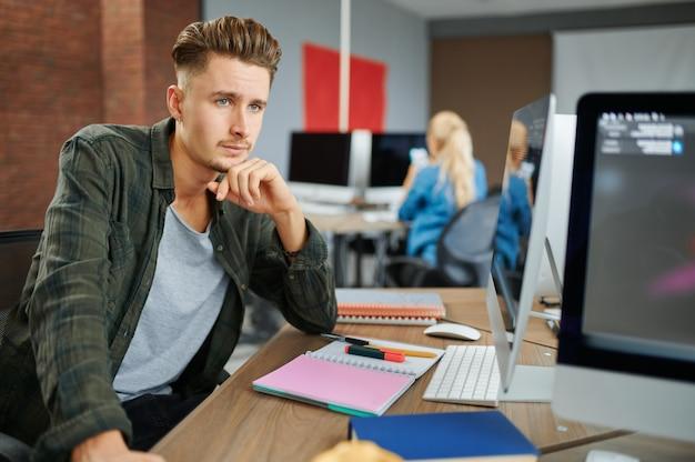 За столом в офисе сидит вдумчивый ит-специалист мужского пола. веб-программист или дизайнер на рабочем месте, творческое занятие. современные информационные технологии, корпоративная команда