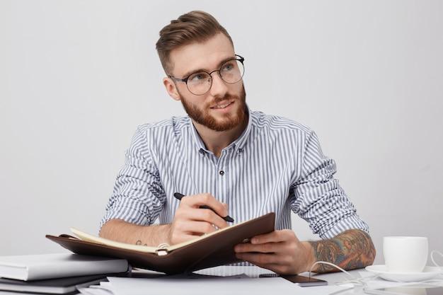 Задумчивый менеджер-мужчина в круглых очках, в строгой рубашке, пишет в блокноте, сидя на рабочем месте,