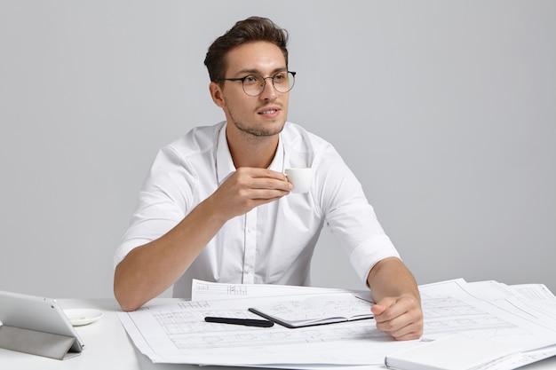 思いやりのある男性のマネージャーは一杯のコーヒーを保持し、しんみりと遠くを見つめ、彼の将来の行動を計画し、webページにテンプレートを描画する方法を考え、素晴らしいアイデアを持っています。設計と建設のコンセプト