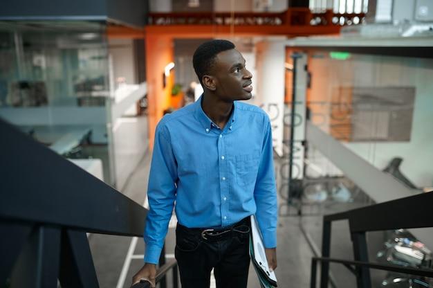 계단에 있는 사려 깊은 남성 관리자, it 사무실에서 개발 중인 아이디어. 전문 작업자, 계획 또는 브레인스토밍. 성공적인 사업가는 현대 회사에서 일한다