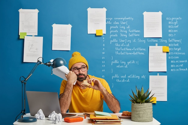 Thoughtful male programmer or software developer ponders on program code, looks away and eats burger, holds papers wears yellow clothes spends time for making project.