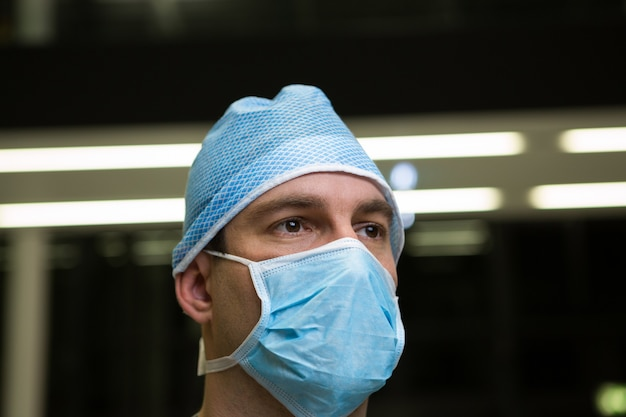 Thoughtful male surgeon wearing surgical mask