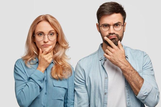 Вдумчивые коллеги мужчина и женщина держатся за подбородки и, сосредоточившись на решении проблемы, смотрят прямо