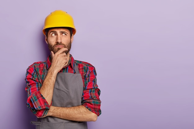 Thoughtful man builder construction touches chin