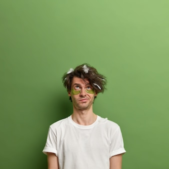 上に集中している思いやりのある男性は、目の下にコラーゲンパッチを適用した後、素晴らしい効果を待ちます、羽毛で髪をとかしていない、緑の壁に対してポーズをとる、あなたの昇進のためのスペースをコピーする
