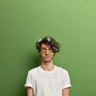 Uomo premuroso concentrato sopra, aspetta un bell'effetto dopo aver applicato cerotti di collagene sotto gli occhi, ha i capelli spettinati con piume, posa contro il muro verde, copia spazio per la tua promozione