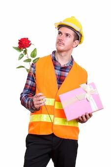赤いバラとギフトボックスを保持している思いやりのある人の建設労働者