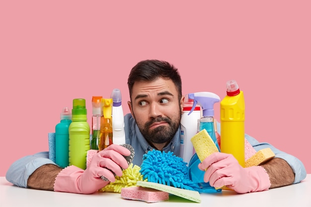 Thoughtful man feels overworked with house cleaning, looks pensively aside, sits at desk with chemical products