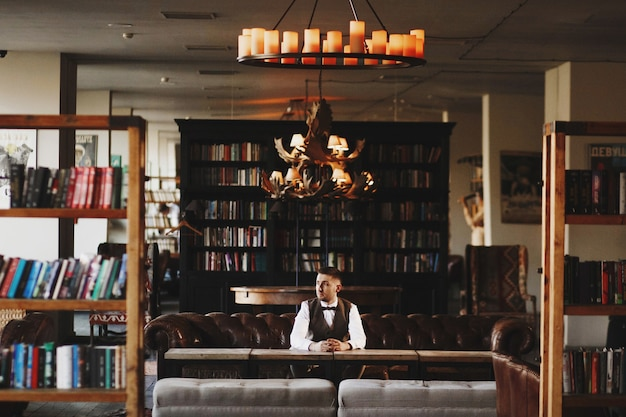 Thoughtful man in grey waistcoat poses in the dark library