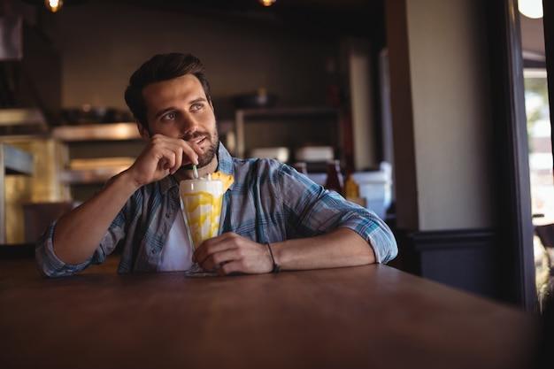 Thoughtful man having milkshake