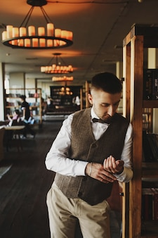 회색 양복 조끼에 사려 깊은 사람은 어두운 도서관에서 포즈
