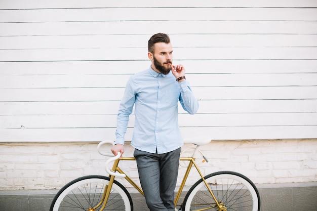 壁の近くの自転車に傾いている思慮深い男