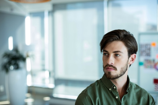Thoughtful man looking away in office