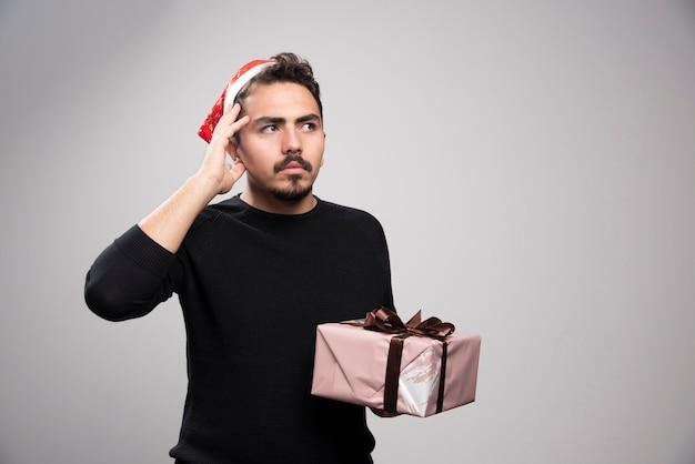 Un uomo premuroso con il cappello di babbo natale in possesso di un regalo di capodanno.