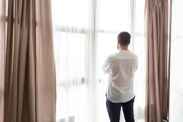 Thoughtful man standing by window