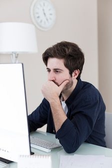 Thoughtful man using computer in office