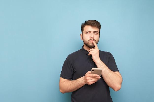 Задумчивый мужчина с бородой стоит на синем со смартфоном в руке, смотрит в сторону и думает в темной футболке