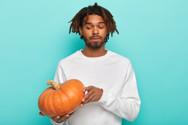 Thoughtful man with dreads, holds pumpkin, prepares for halloween, wears white sweater, has beard
