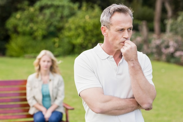 Thoughtful man with girlfriend sitting behind in the garden